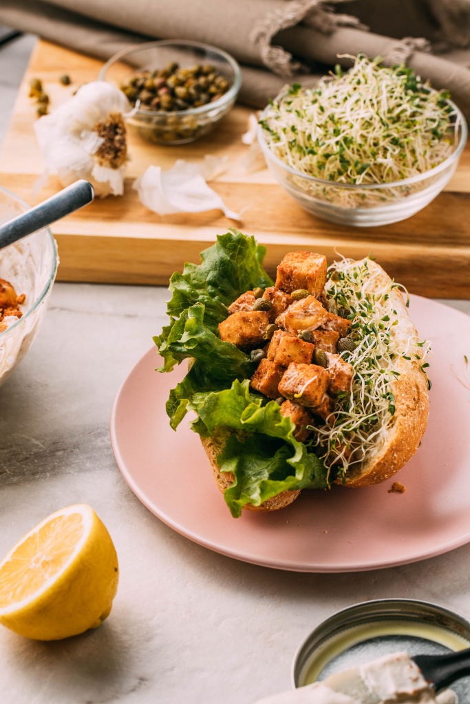 Vegan Tofu Lobster Roll gluten-free sandwich recipe pink plate cutting board sprouts lemon garlic plant-based tandoori masala seasoned  tofu recipes for meatless seafood wfpbno recipes