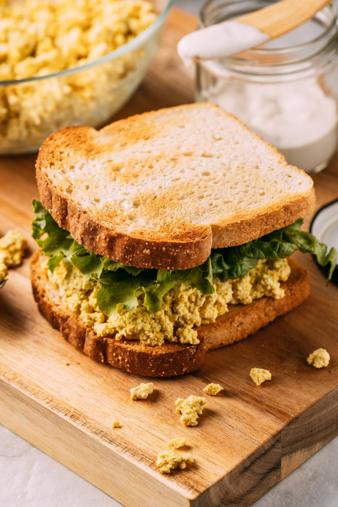 whole food plant based egg salad sandwich on gluten free bread lettuce oil-free mayonnaise on spreader