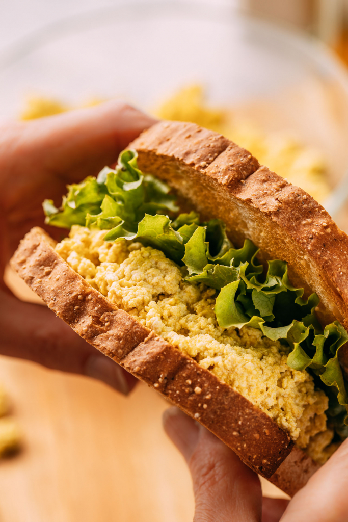 vegan pressed tofu egg salad sandwich with lettuce held in hands