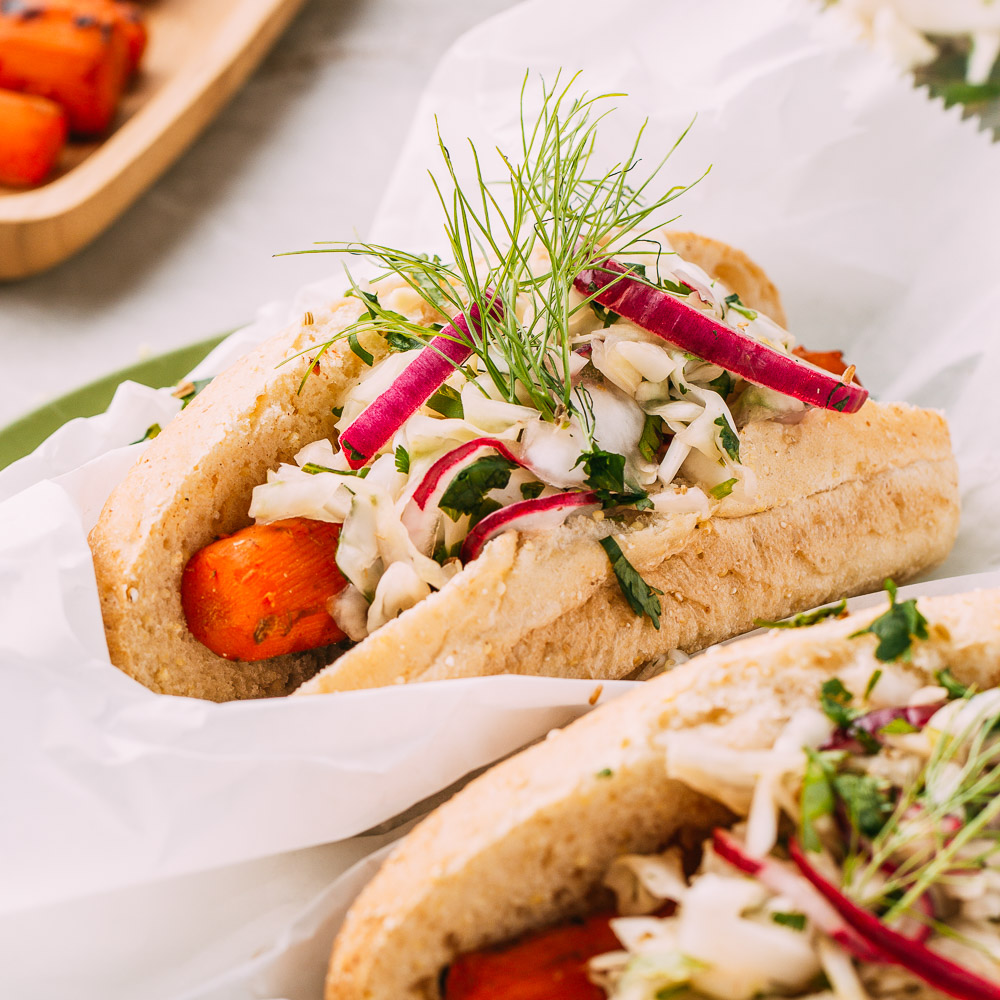 vegan carrot hot dogs or slaw dogs on gluten-free bread with topped coleslaw with red onion and a sprig of fennel