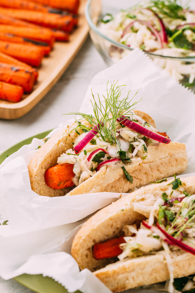row of grilled carrots and two vegan hot dogs with slaw and gluten-free buns topped with secret coleslaw made with crunchy fresh fennel