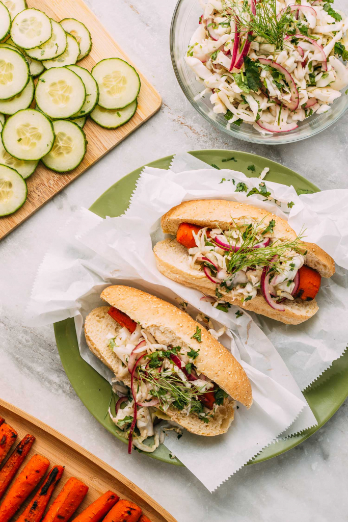 multiple plant-based hot dogs with slaw on a green plate and white paper wrappers in gluten-free vegan buns topped with secret coleslaw