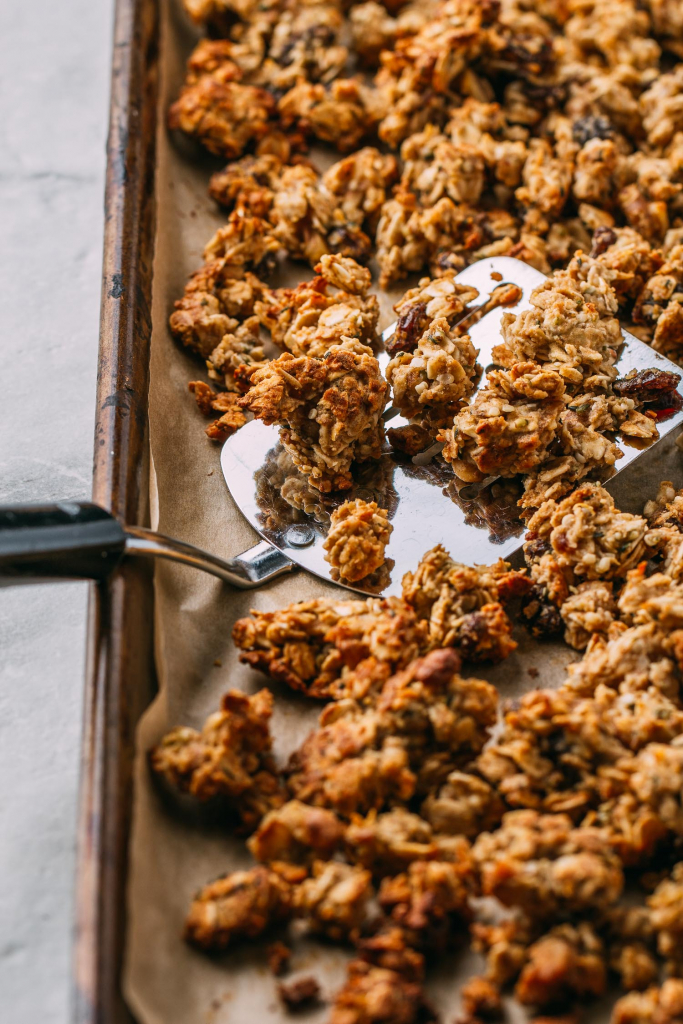 spatula scooping up freshly baked granola off of a baking sheet