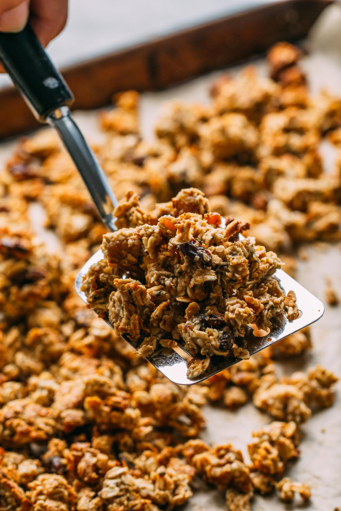 baking pan filled with homemade granola and a spatula full