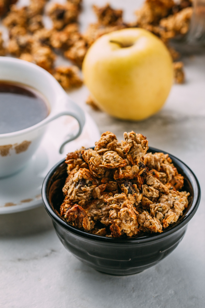 a small bowl healthy vegan granola cup of coffee and yellow apple