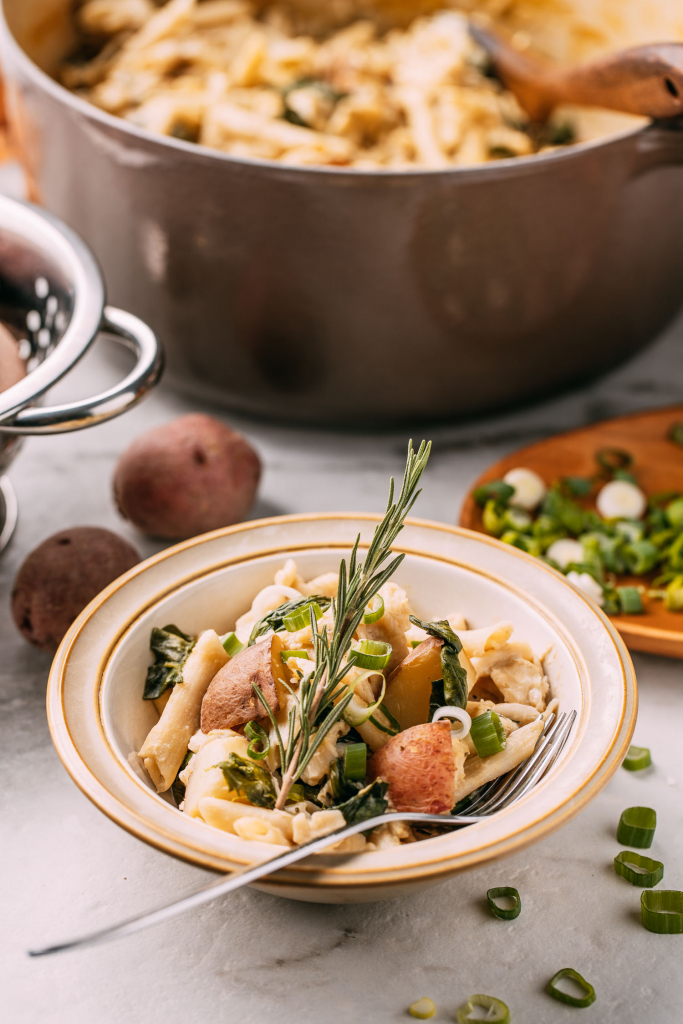 a kitchen scene with a le creuset Dutch oven in the background and a bowl filled with easy vegan comfort food of potatoes and Italian pasta and a fork