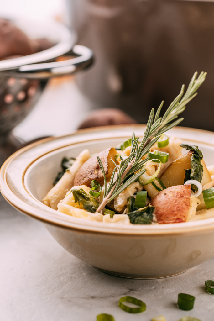 hearty plant-based potatoes with pasta garnished with a stem of fresh rosemary