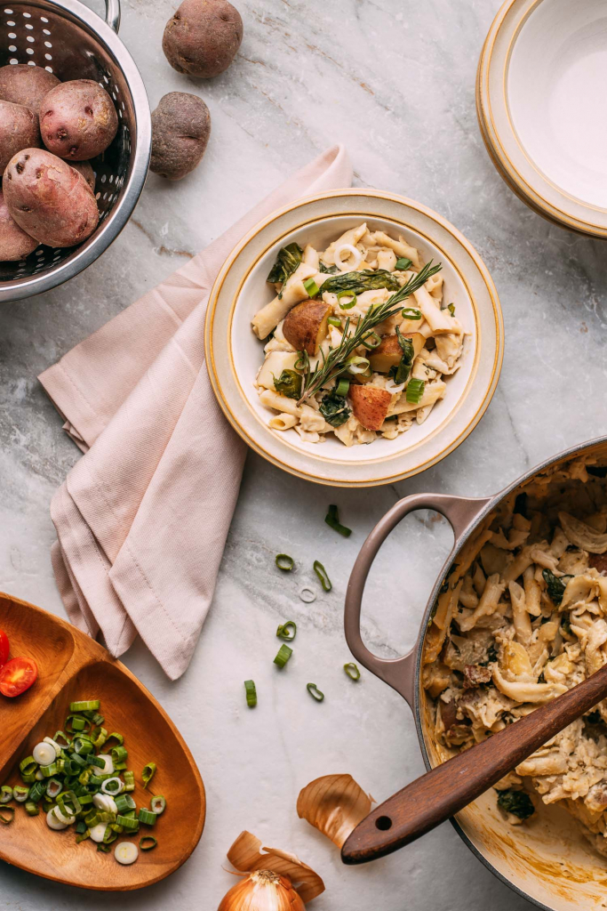 marble background kitchen setting with potatoes and pasta in le creuset dutch oven wooden spoon pink napkin and pasta with green onions slices into circles on side in wood bowl
