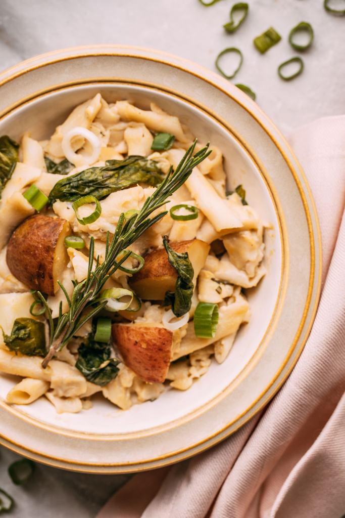 a bowl of potatoes and pasta with a creamy dairy-free cheese sauce and herbs with a pale pink napkin