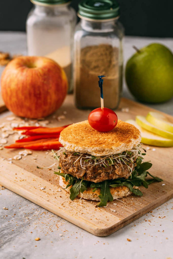 healthy gluten-free sausage sandwich sits on cutting board with apples spice jars and red pepper slices in background