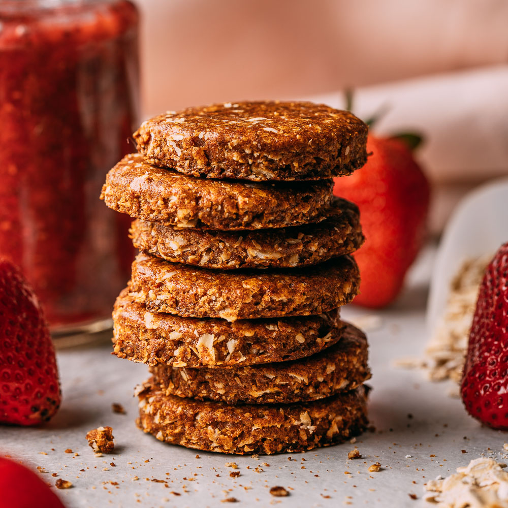 a tall stack of seven vegan oatmeal date cookies strawberry jam in background