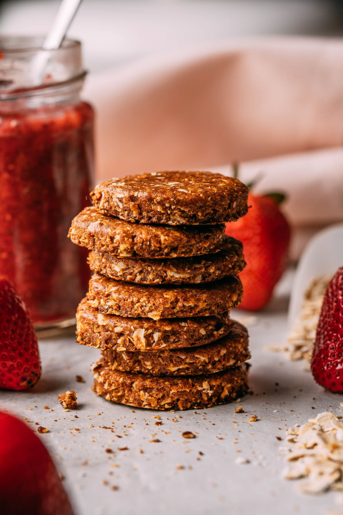 homemade vegan gluten-free cookies in a stack with a strawberry behind crumbs pink napkin