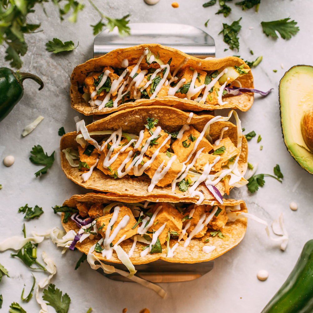 row of three vegan buffalo tofu tacos corn tortillas in silver rack cilantro leaves avocado half with pit drizzled in vegan blue cheese dressing with playful drips of dressing around it | Veeg