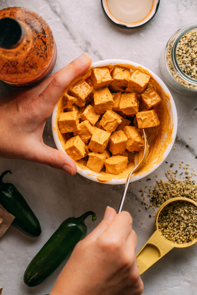 bowl of tofu being stirred coated in orange red oil-free vegan buffalo sauce bottle of sauce on side jalapenos hemp seeds measuring cup