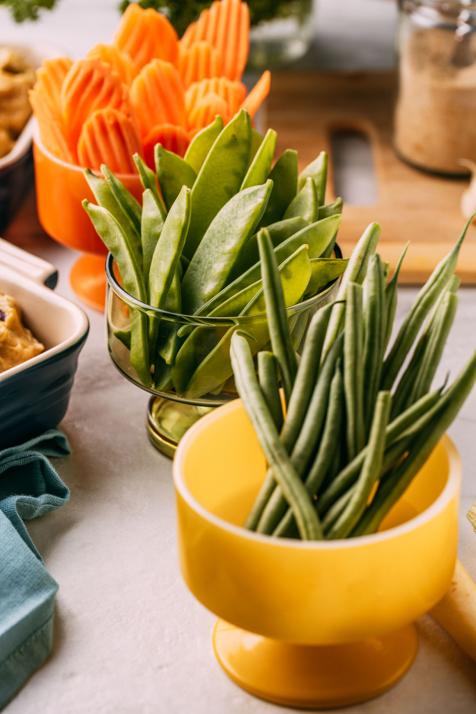 yellow mid century footed bowl of green beans  and two others with snow pea pods sliced ridged carrots sitting on marble counter surface  like a buffet for party