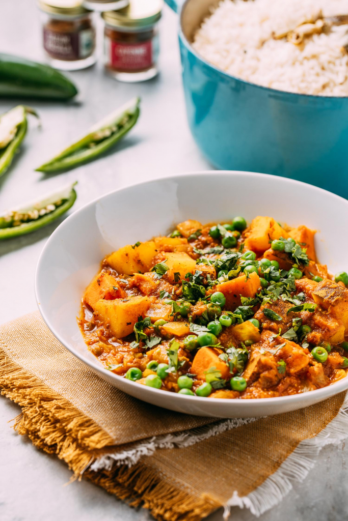 Indian potatoes peas curry in white bowl yellow gold napkin green peppers blue pot of rice