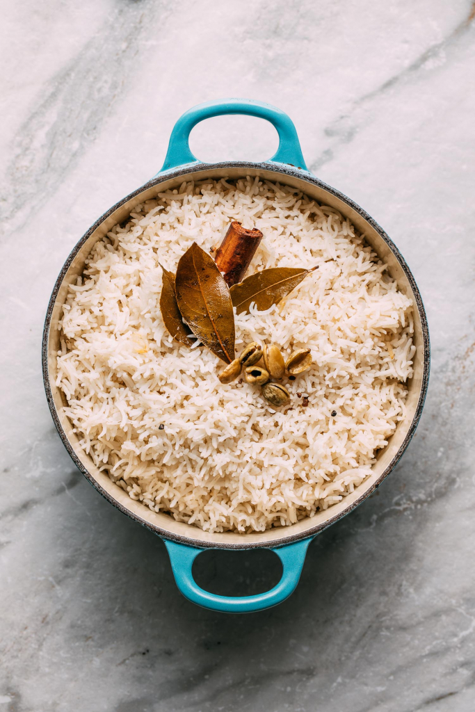 blue handled le creuset pot of creamy white cardamom rice with herbs f bay leaves and a cinnamon stick on marble background