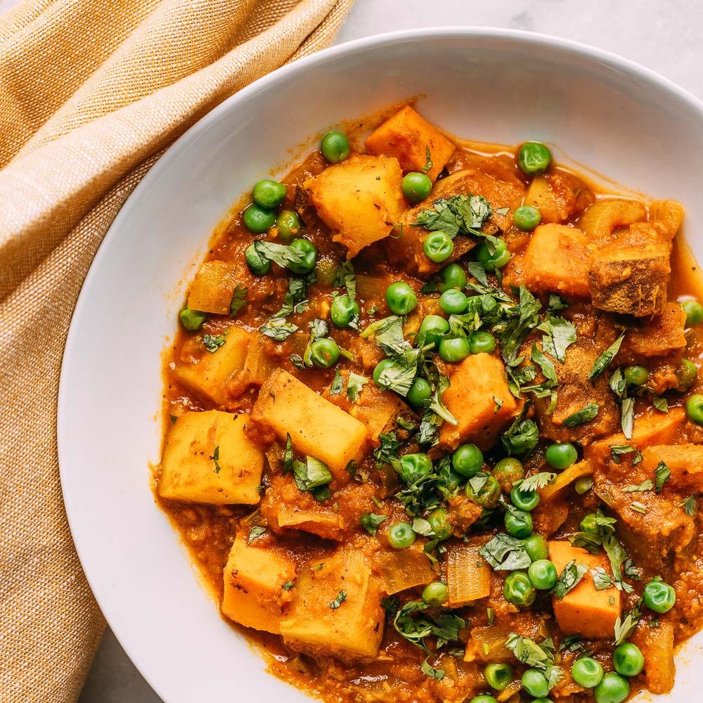 white bowl potato pea curry topped with sprinkle green cilantro | Veeg