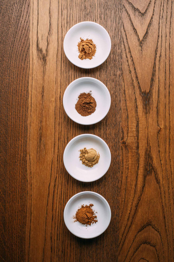 creative minimalist lineup of 4 white bowls holding ground spice brown wood table