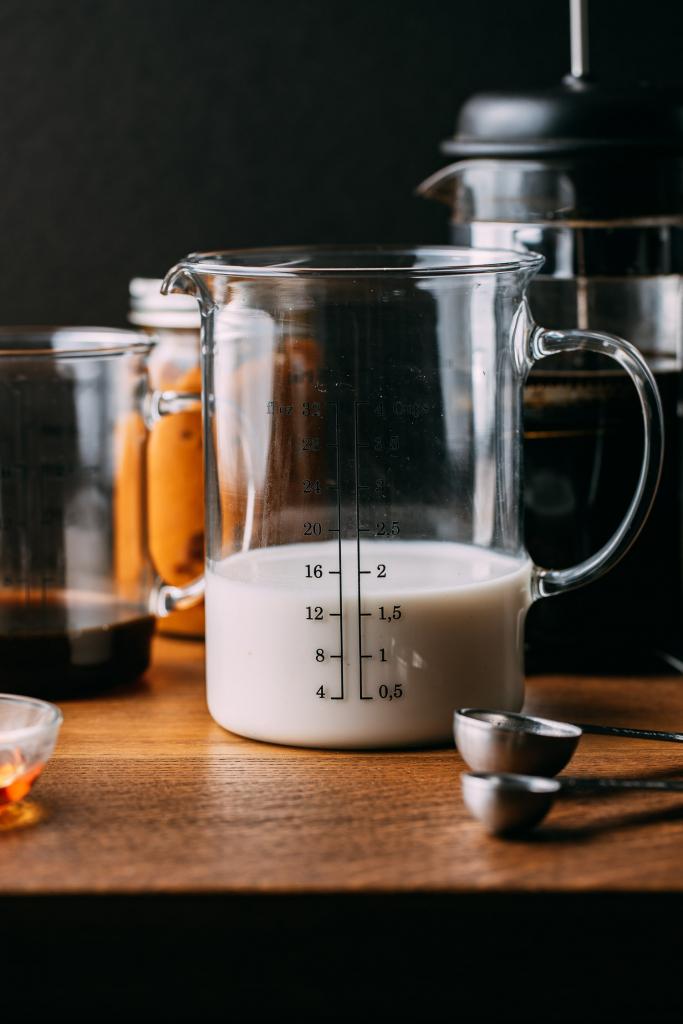 low fat pumpkin spice latte measuring cup of vegan milk measuring spoon coffee pot