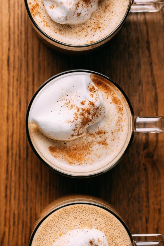 overhead of three plant-based vegan pumpkin spice lattes with pumpkin pie spice