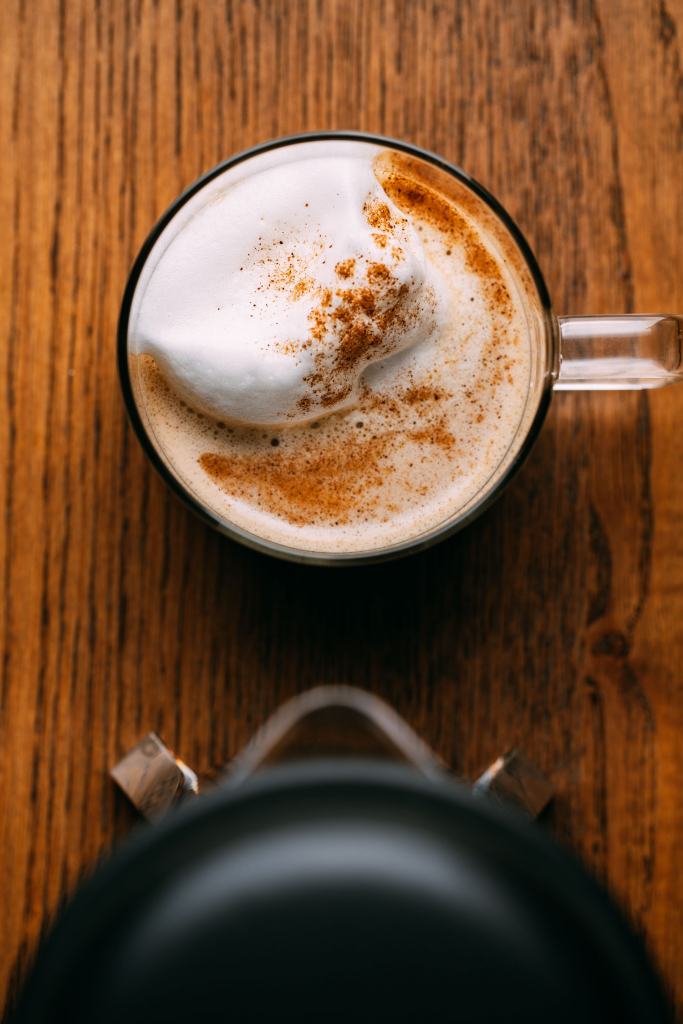 low fat pumpkin spice latte foamy cream topping on brown wood with black offee press