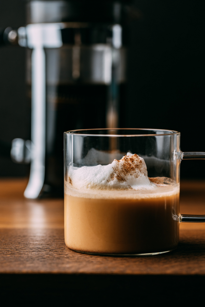 plant based pumpkin spice latte with whip cream french coffee press wood table black background