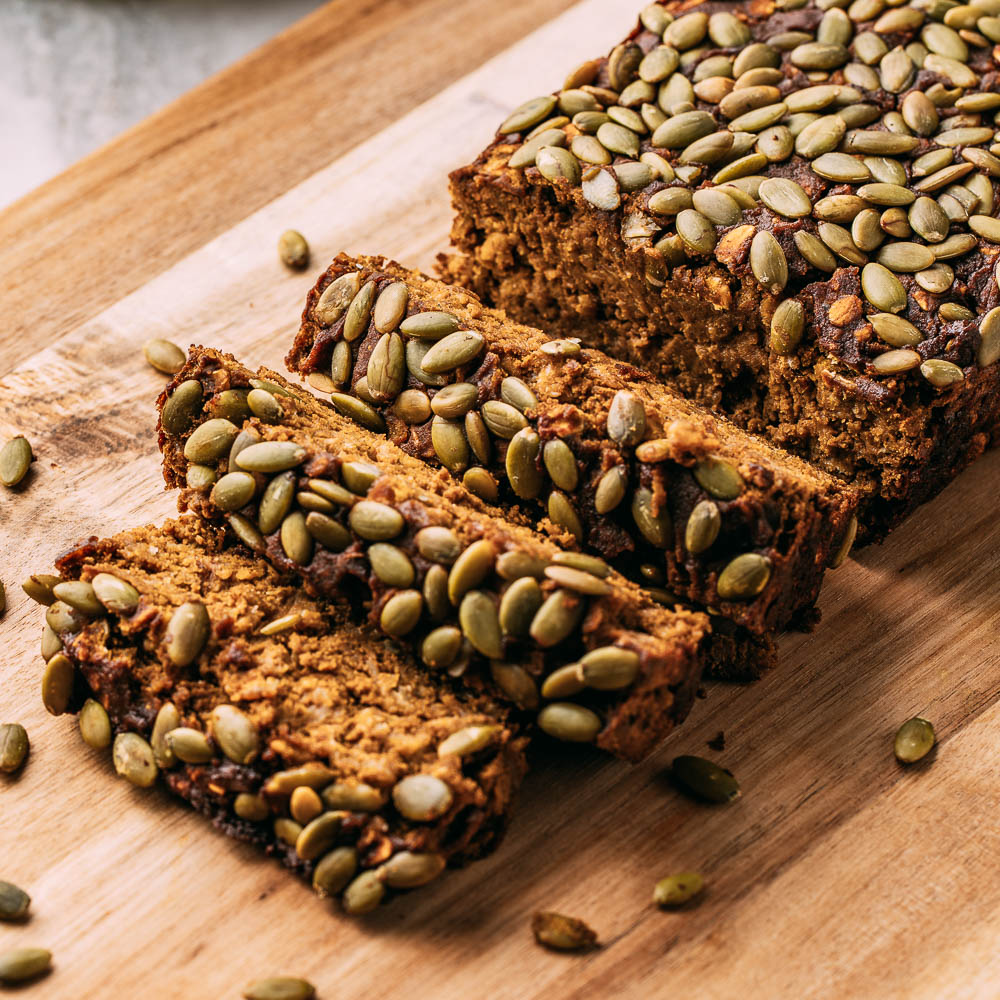 three slices of vegan gluten-free pumpkin bread cut from whole loaf topped with pumpkin seeds on wood