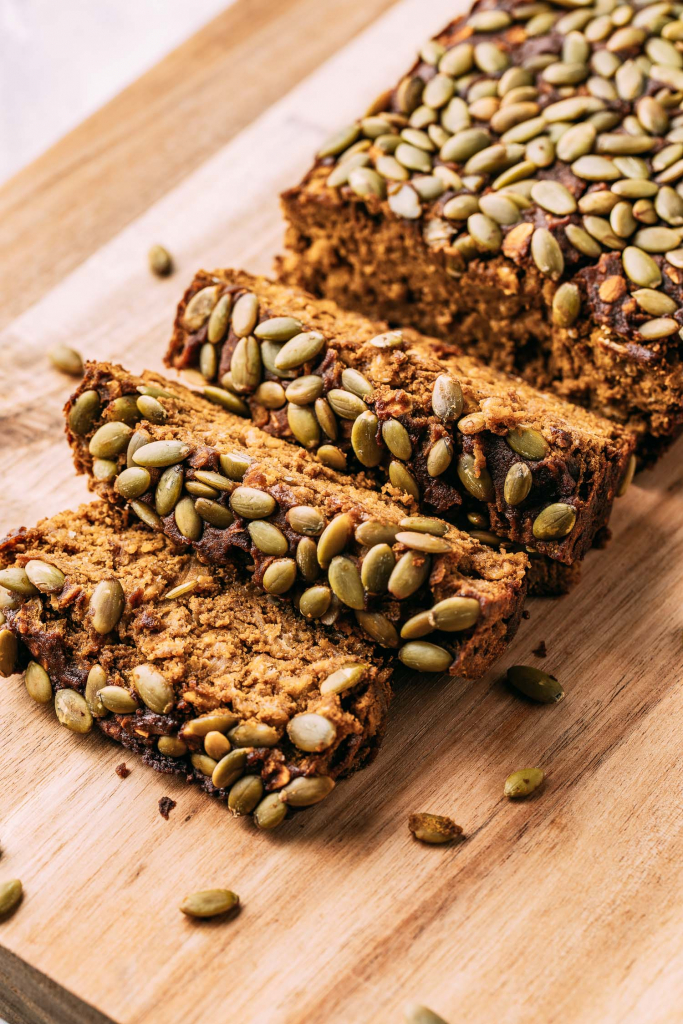 dark orange colored pumpkin seed topped loaf of pumpkin bread partially sliced on cutting board