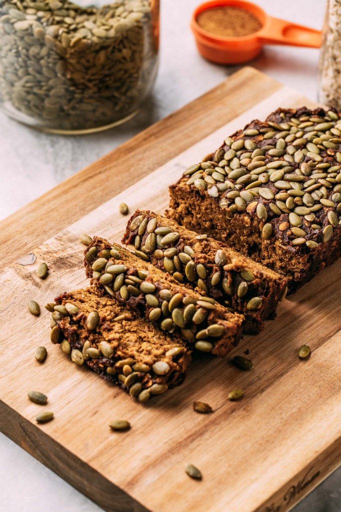 vegan gluten-free pumpkin bread being sliced with seeds scattered on cutting board with orange measuring cup and jar of seeds