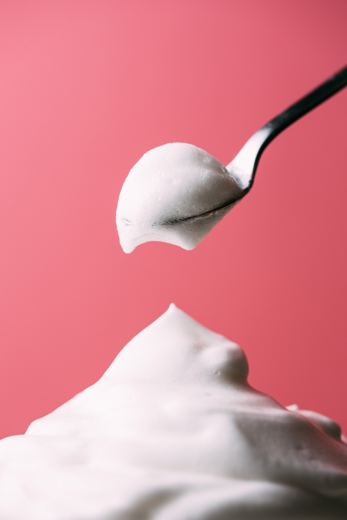 pink background spoon dipping white creamy vegan cool whip topping from mountain pile of whipped cream