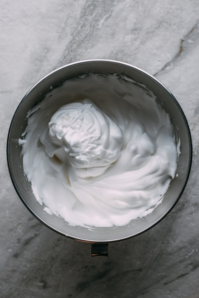 stainless steel bowl of creamy white vegan gluten free whipped cream cool whip topping gray white marble counter