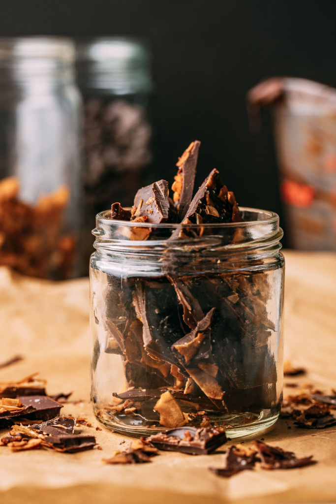 tan color parchment paper surface glass jar vegan chocolate bark with vegan bacon topping glass jars background cooking scene