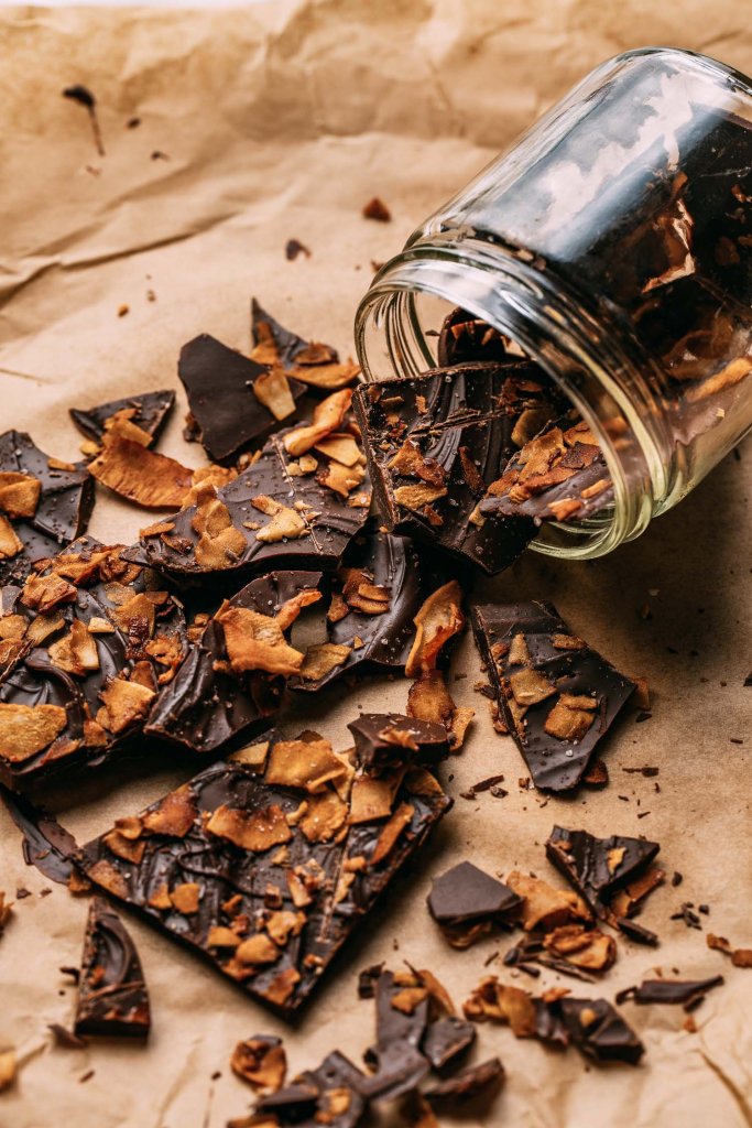 a spilled clear glass jar of homemade chocolate candy in irregular shapes on brown baking paper background