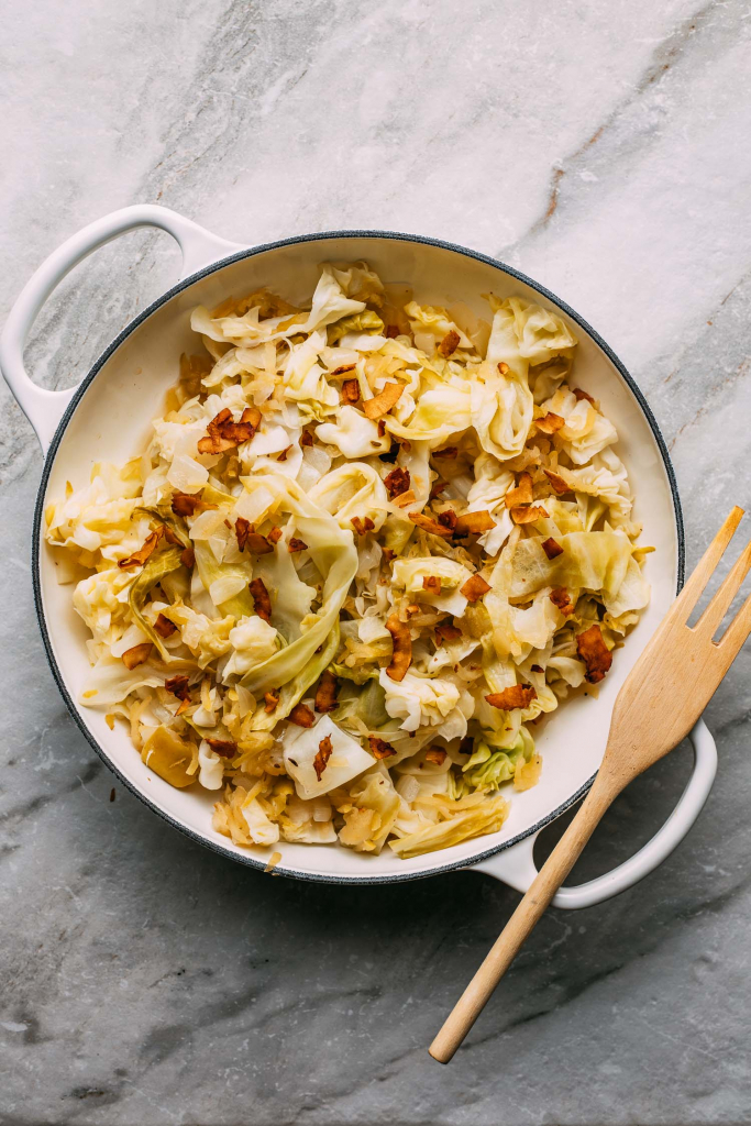 round white pan with two handles of cooked cabbage and plant-based bacon recipe on gray background