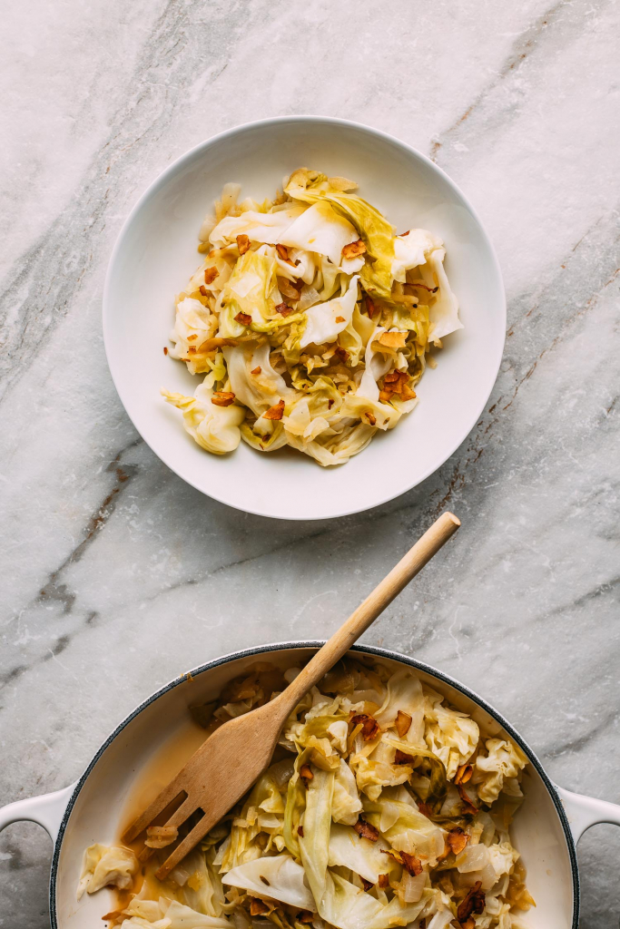 gray marble background white bowl of cooked cabbage topped with bacon in center half view of cook pan and fork at bottom