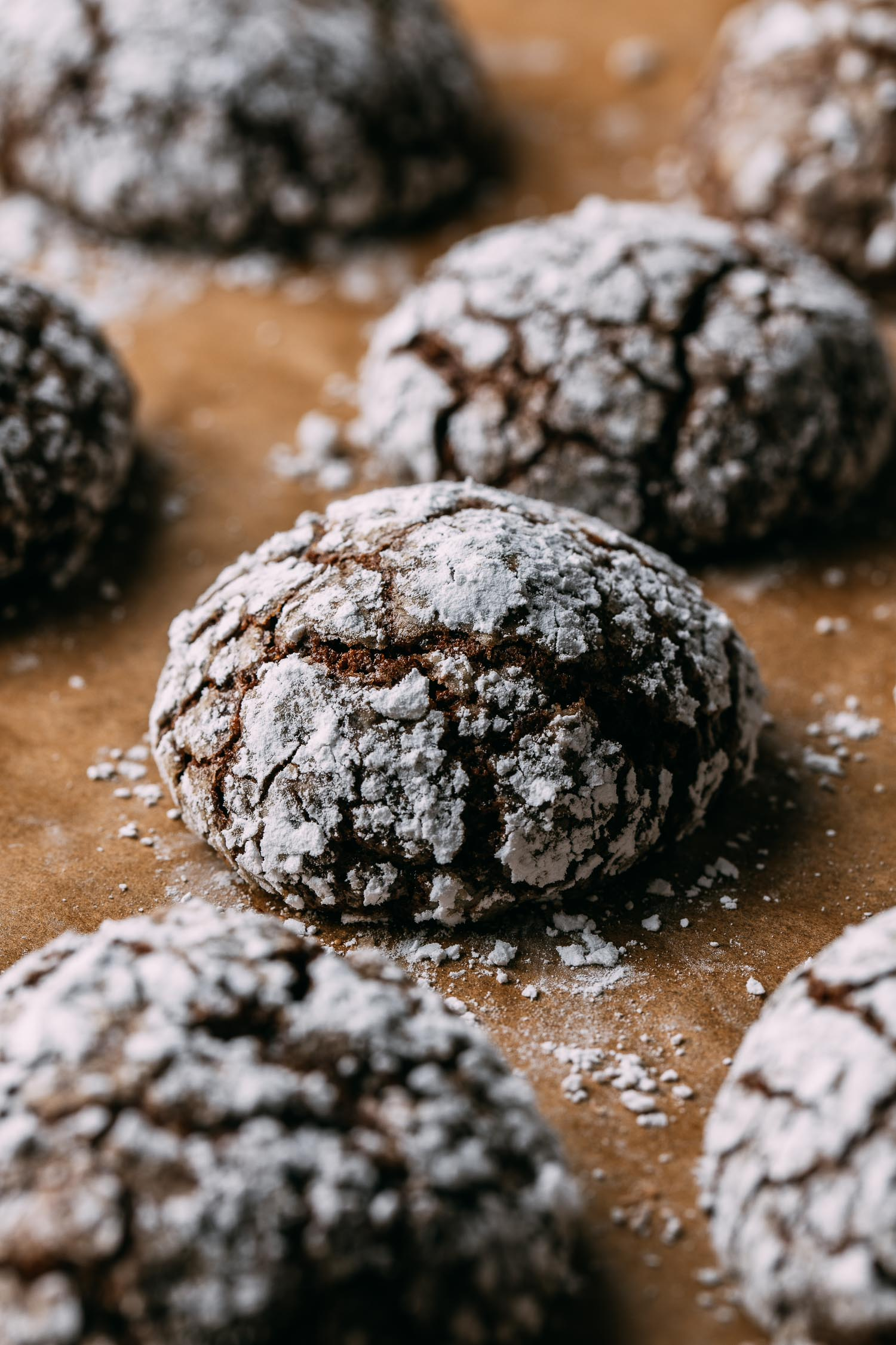 chocolate crinkle crackle cookies sitting at angle on parchment paper