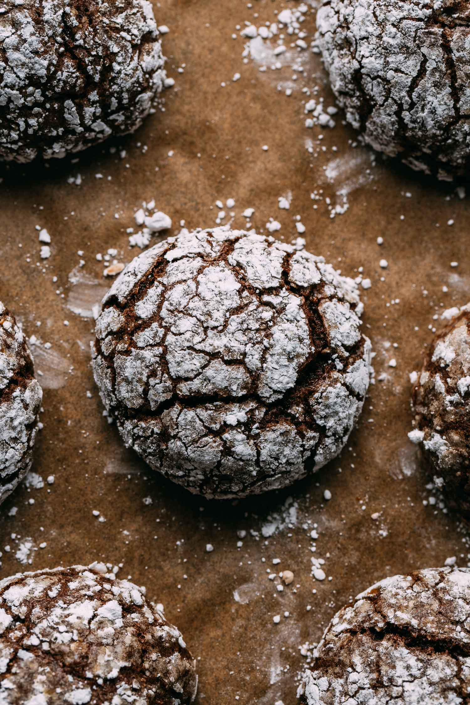 sheet pan of cookies one in center view powdered sugar scattered for eggless chocolate brownie cookies