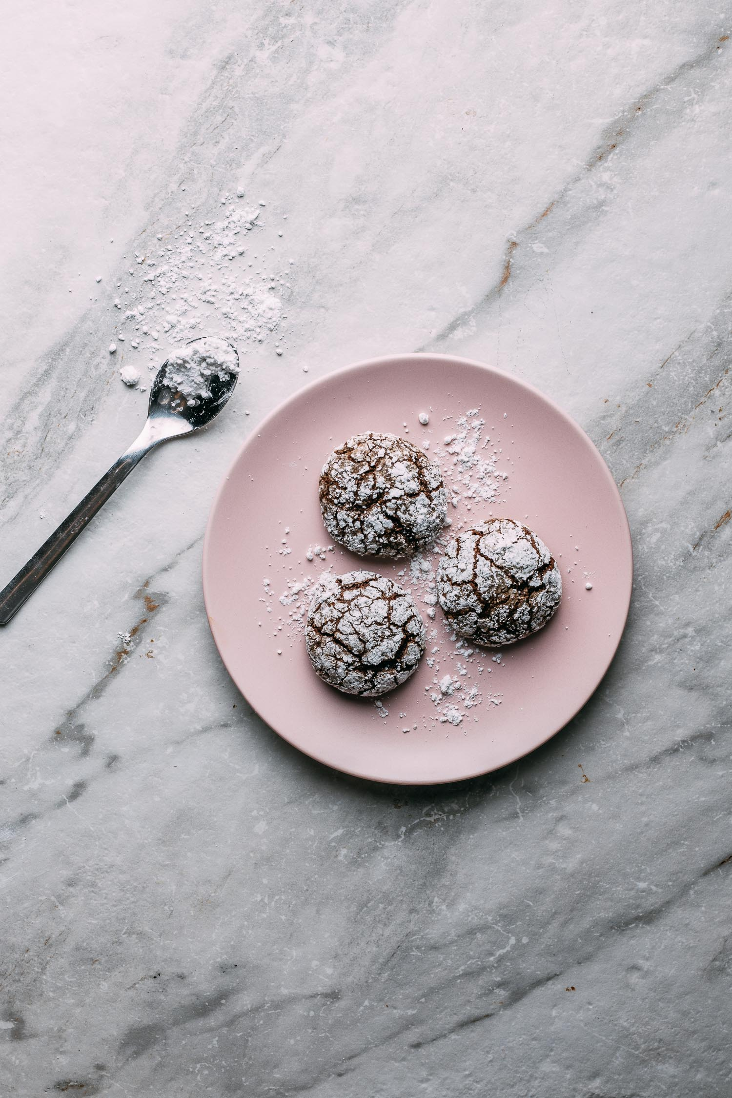 gray marble background pink plate of chocolate cookies covered in white powdered sugar  spoon on side