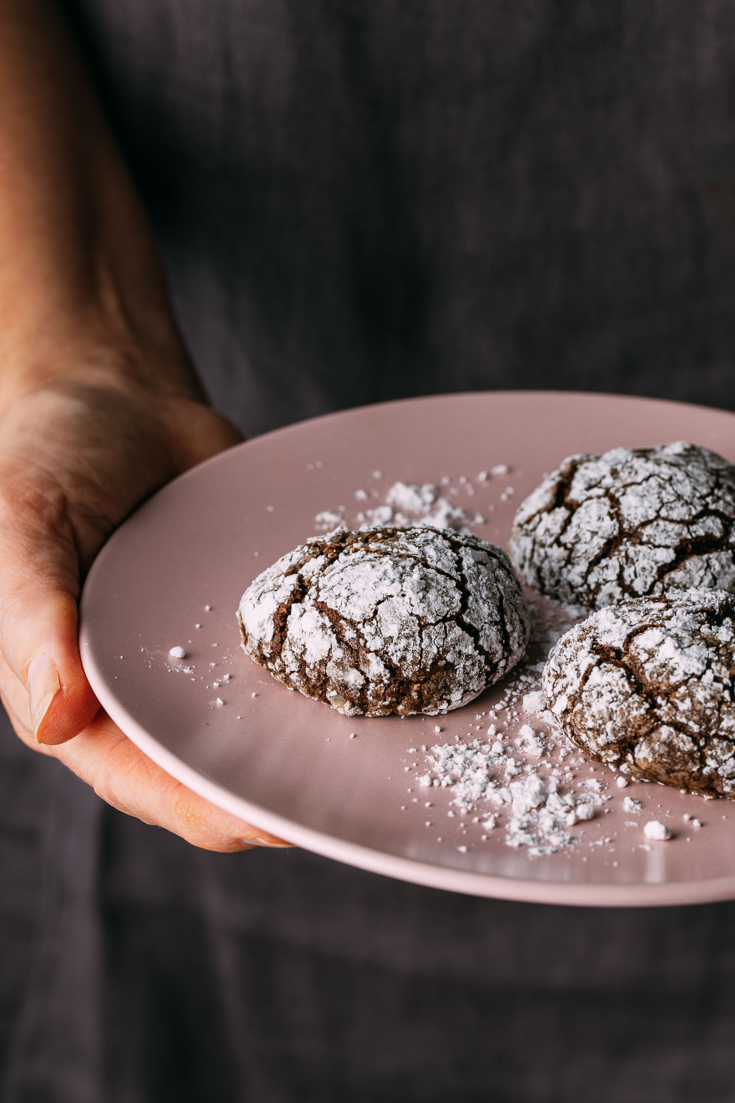 pink plate held in hand gluten-free vegan chocolate crinkle cookies sprinkle powder sugar