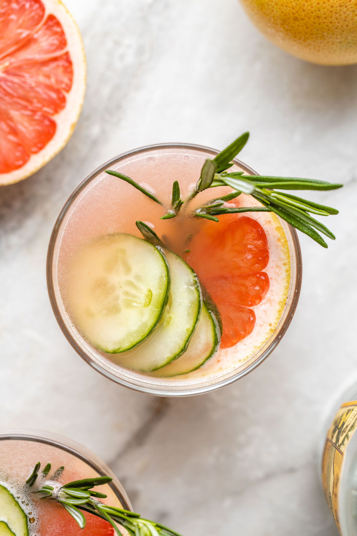 pink low carb gin and juice cocktail with cucumber slices and rosemary sprig