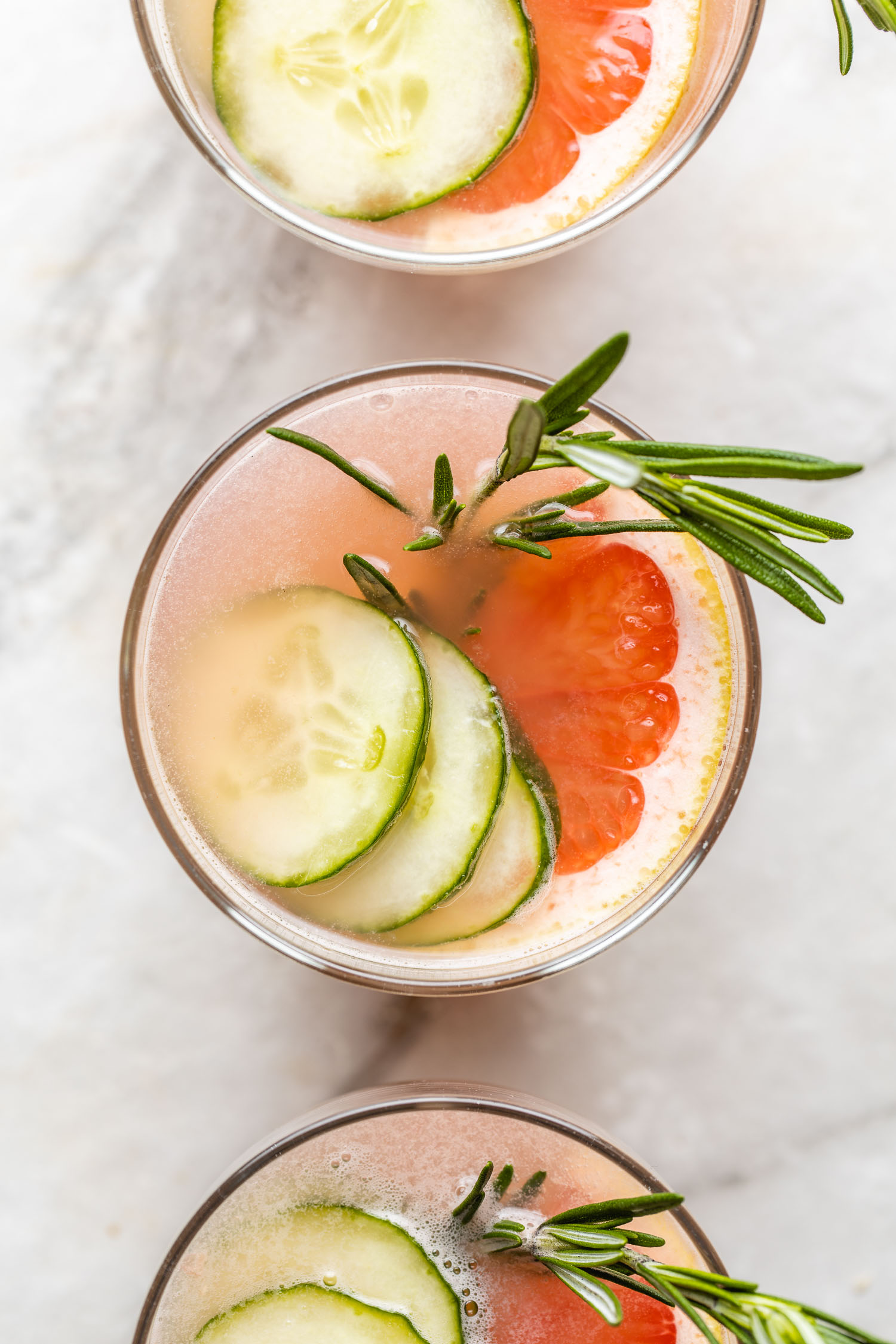 three glasses  low carb gin and juice mixed drinks with green cucumber pink grapefruit and rosemary sprig white background marble