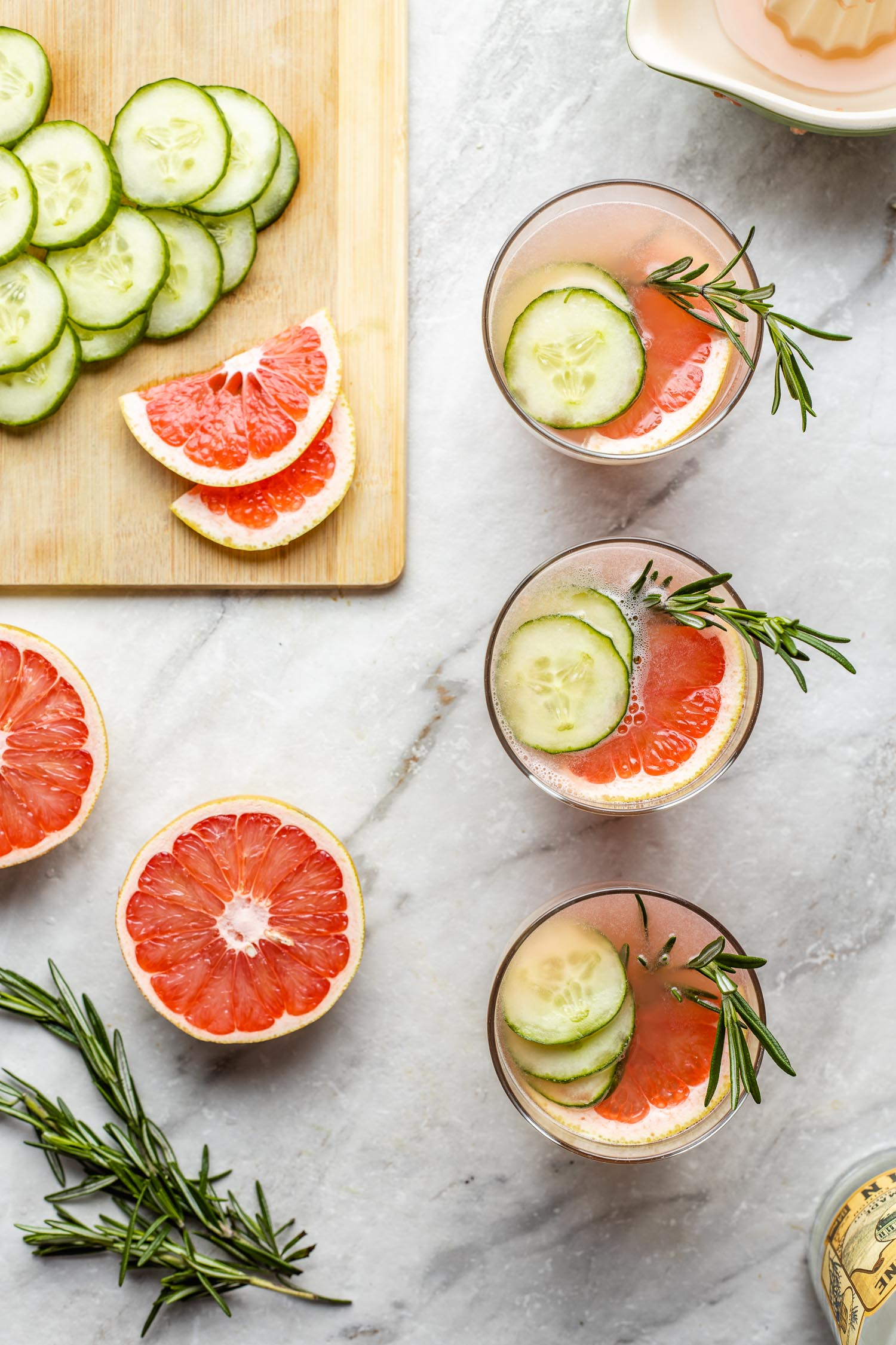low carb gin and juice cocktails marble surface cutting board with garnishes grapefruit half