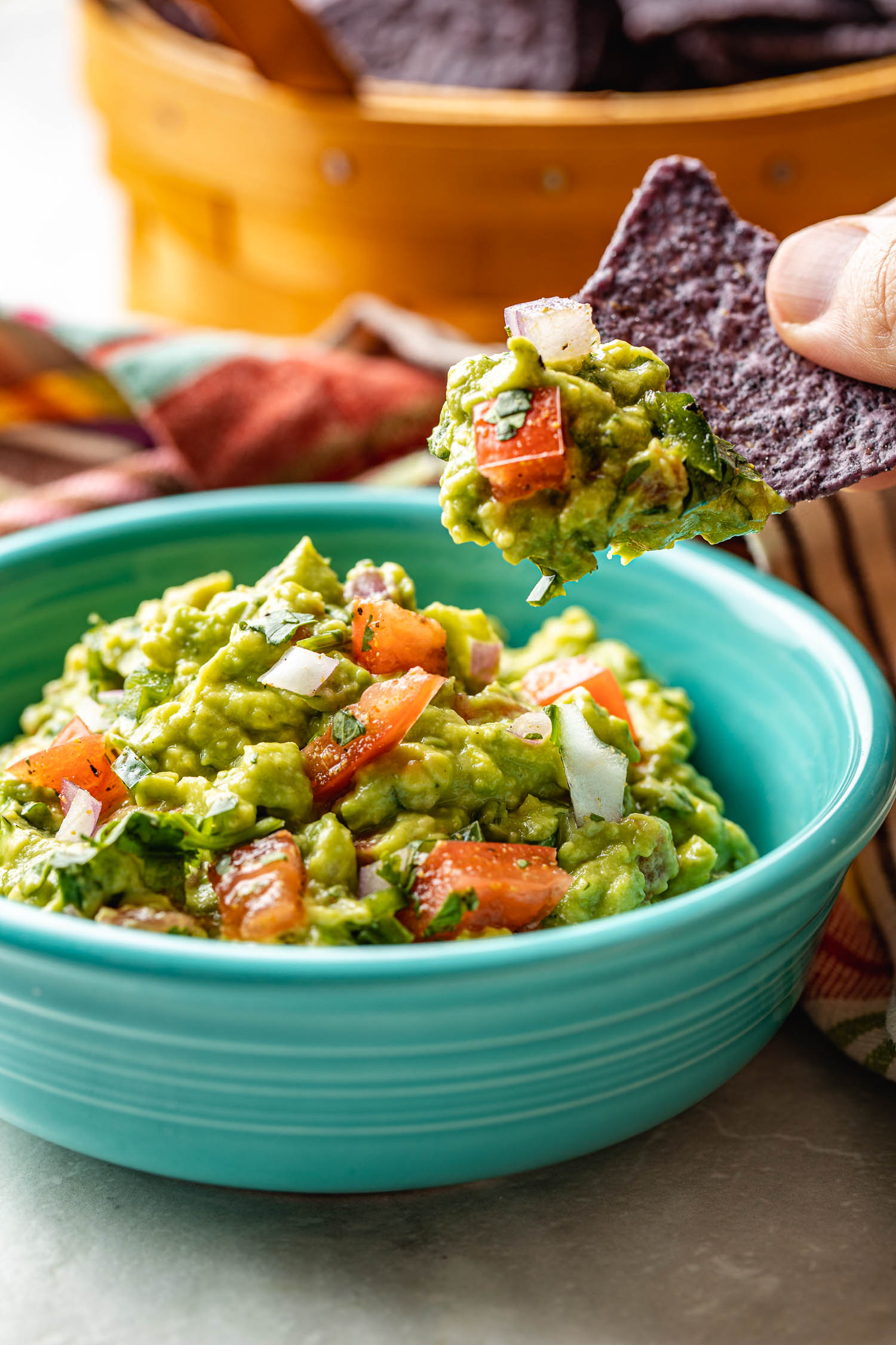 homemade guac like Chipotle Mexican Grill guacamole  being dipped into by a guy holding blue corn chip