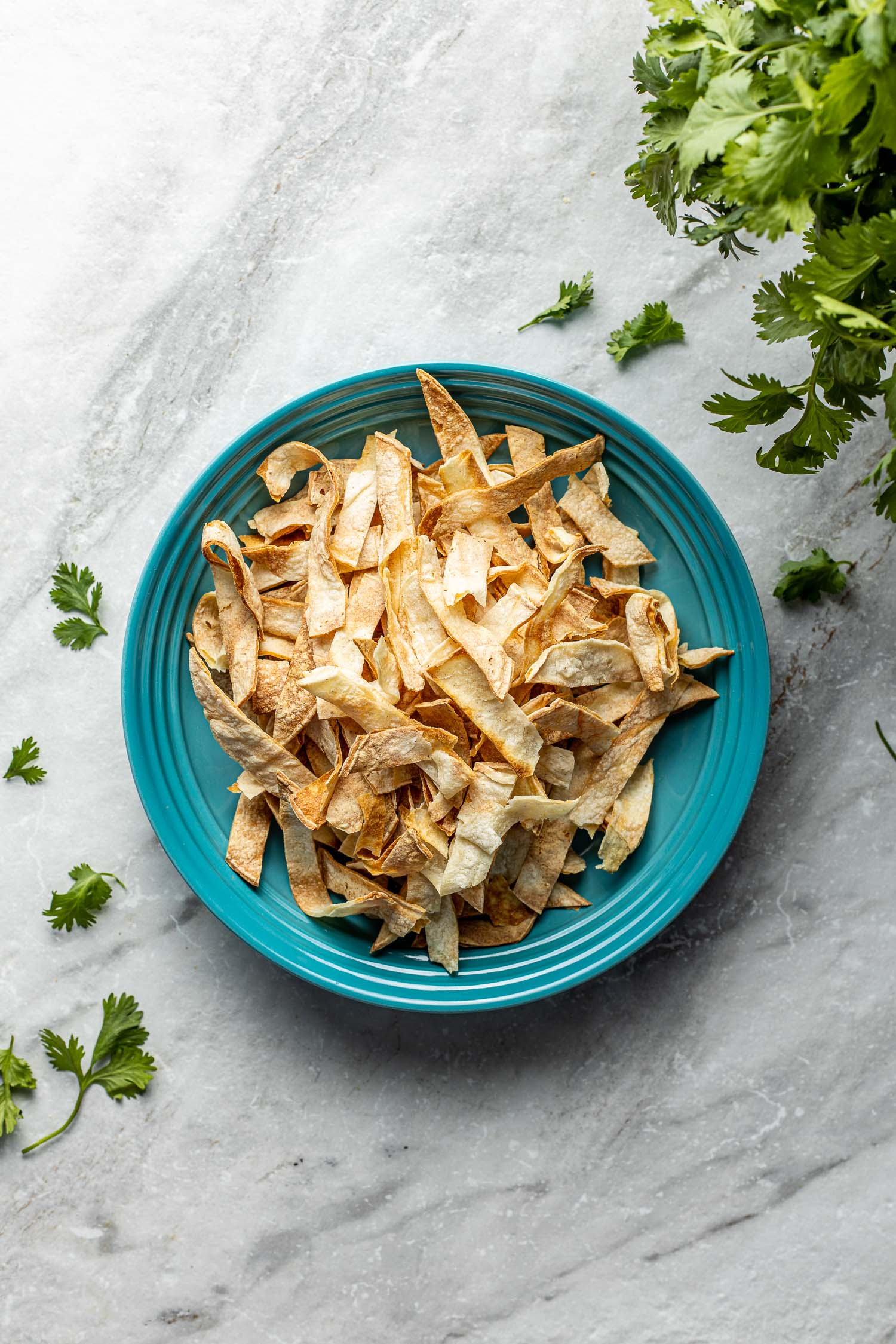 gluten-free chips recipe on gray marble with green herbs coming out of the right corner scattered across to other side
