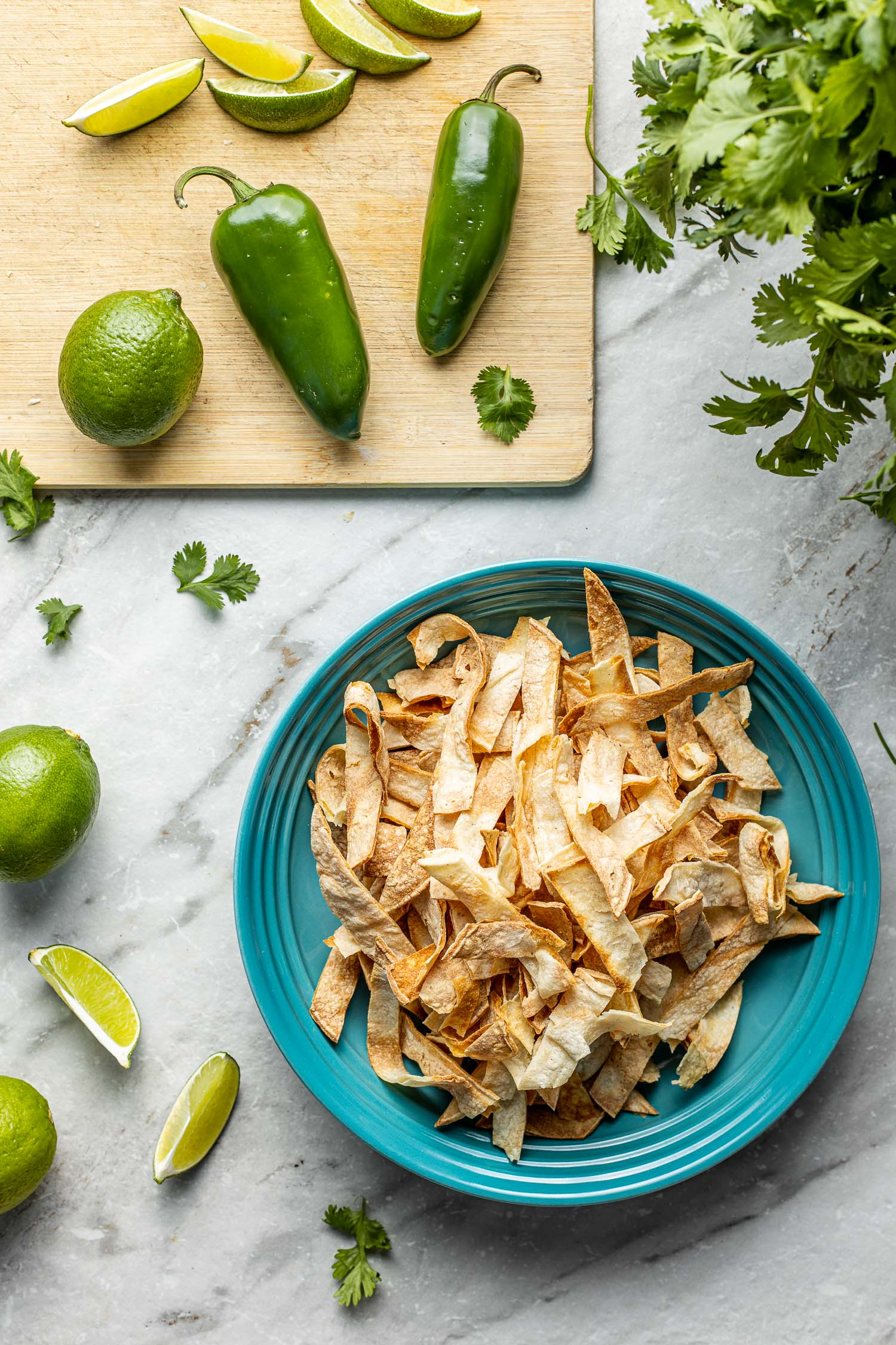 cooking scene with green limes, green peppers, green herbs, turquoise bowl of homemade tortilla chips wood cutting board, marble work surface