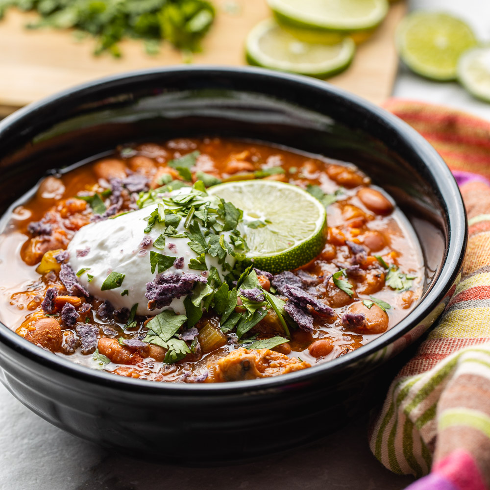 served up in a black bowl with a festive striped colorful napkin and slices of fresh green lime is a bowl of vegan and gluten free instant pot chili with beans | Veeg