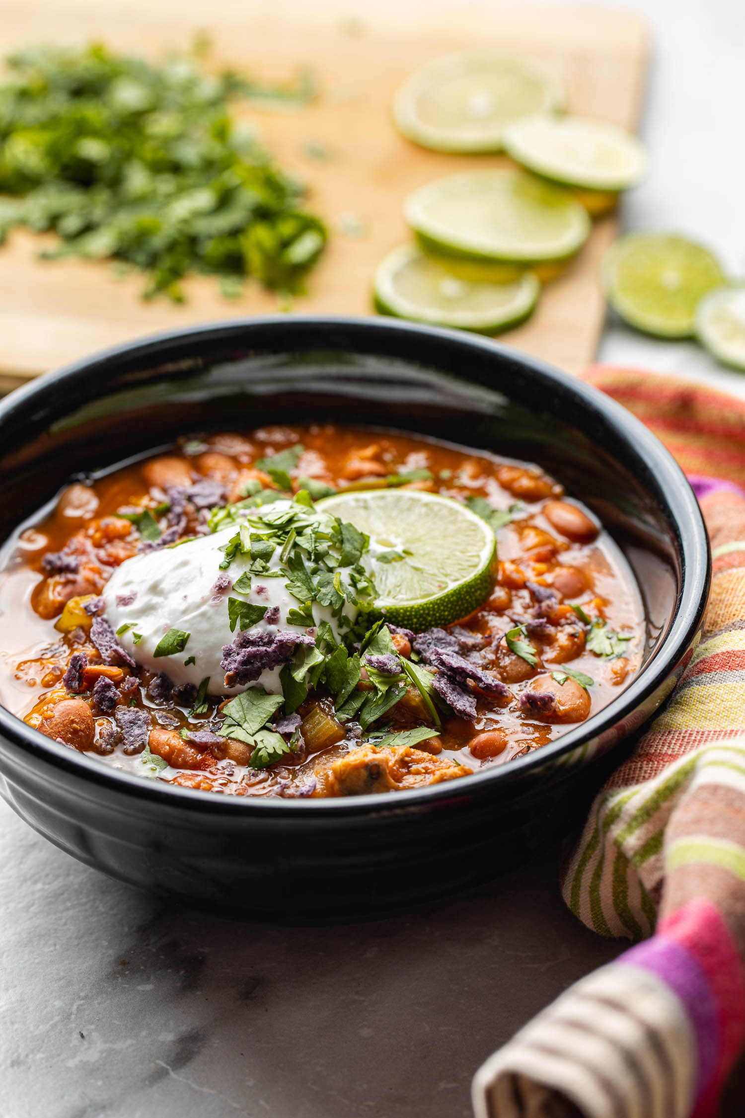 cilantro, limes, and a colorfully striped cotton napkin surround a black bowl filled with chili with sweet potatoes, plant based and gluten free