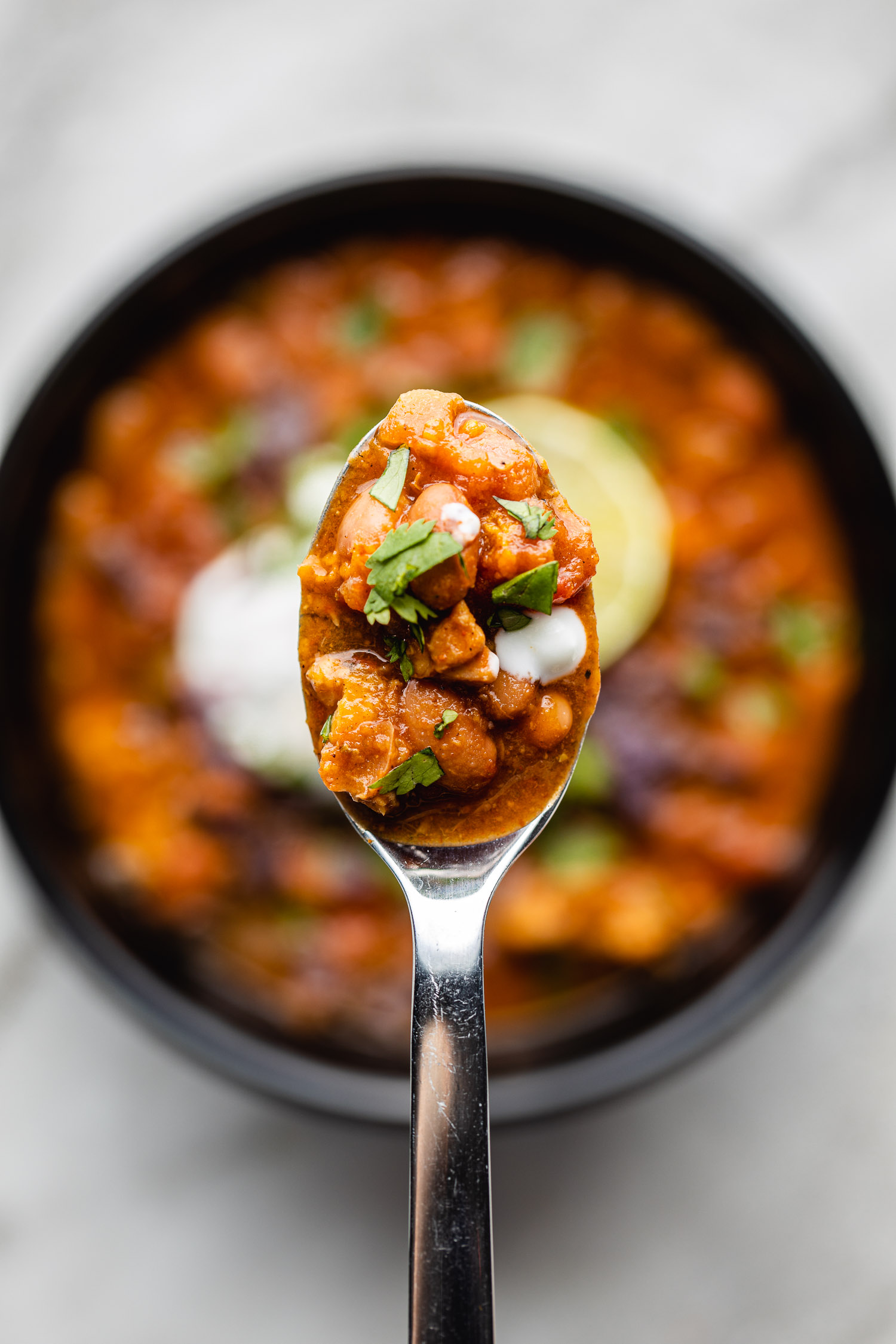 a hearty bowl of chili sits below a spoonful being lifted above it