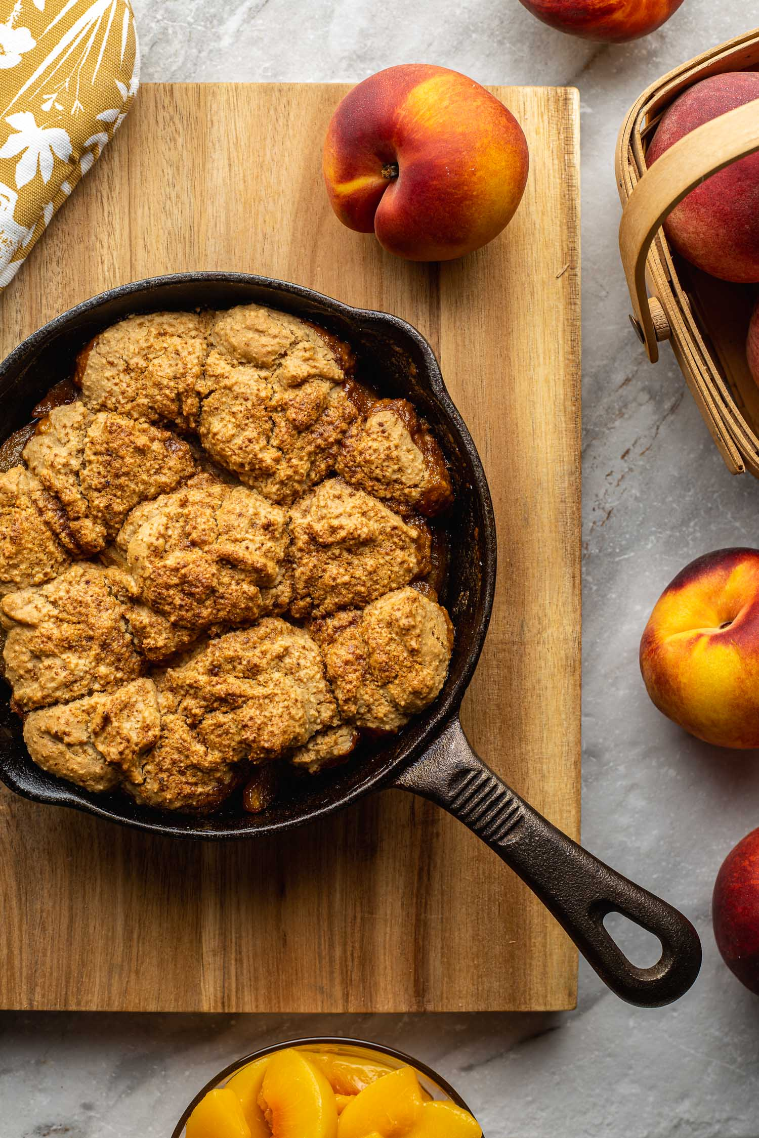 on a wood cutting board sits a cast iron skillet of biscuit topped gluten free peach cobbler with a basket and a whole ripe peach sitting nearby